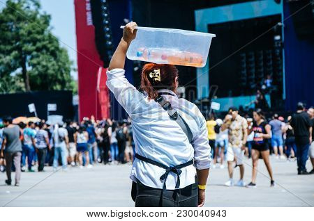 Water Seller With A Box On His Head That Contains Bottles Of Water And Soda