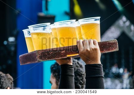 Beer Seller With Many Plastic Cups With Beer In A Wooden Box At A Concert