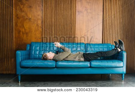 Beautiful Young Man Relaxing On Sofa And Looking On His Smart Phone.a Young Man Lays On A Stylish Bl