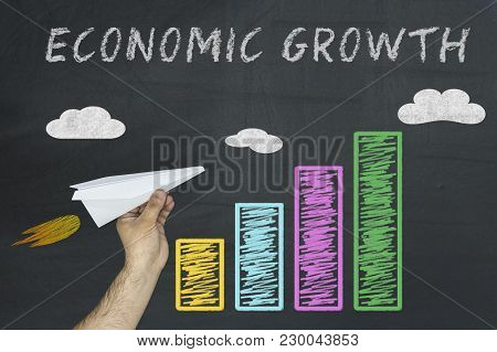 Economic Growth Concept. Hand Holding Plane As Symbol Of Economic Boost. Colorful Business Chart