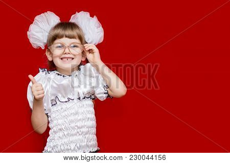 Portrait Of Cheerful Little Girl In Very Big Glasses And White Bows Show Thumb Up. Concept Of Eyesig
