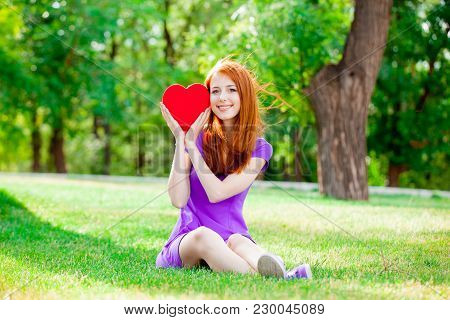 Young Redhead Girl With Heart Shape Toy On Green Summertime Park