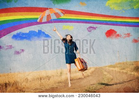 Brunet Girl Fly Away With Umbrella And Suitcase At Countryside. Image Made In Old Color Style
