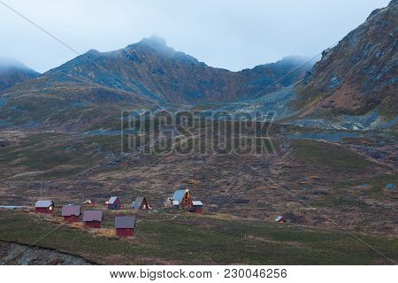 A Cluster Of Homes In A Town In Alaska, High In The Mountains. It Is Morning, And Fog Can Be Seen On