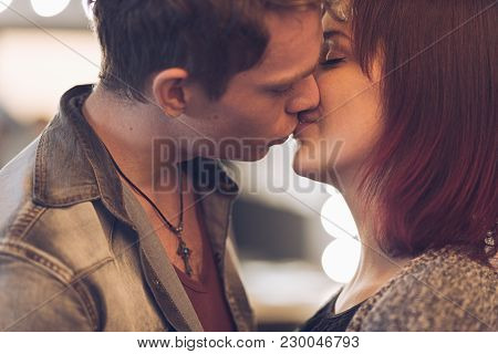 Portrait Young Beautiful Couple Kissing With Lights On Background. Man Kissing Woman On Forehead. In