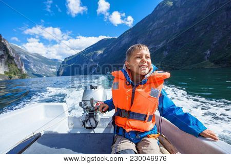 Portrait Of Happy Boy Close Up Driving The Motorboat, Geirangerfjord, Norway. He Is Enjoying The Mom