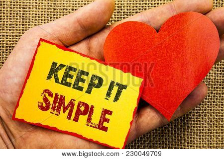 Handwriting text showing Keep It Simple. Business concept for Simplicity Easy Strategy Approach Principle written Sticky Note Paper With Heart Holding Hand with Finger. poster