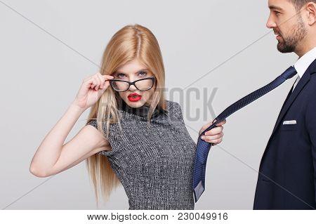 Sexy Blonde Manipulator Woman Pulling Man By Tie, Holding Eyeglasses