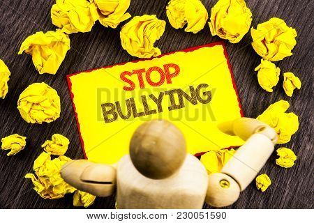 Writing text showing  Stop Bullying. Business photo showcasing Awareness Problem About Violence Abuse Bully Problem written Sticky Note Holding By Sculpture the wooden background poster