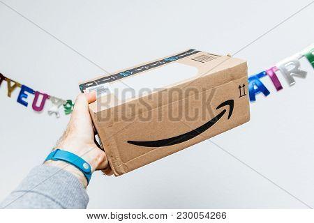 Paris, France - Jan 6, 2018: Amazon Cardboard Parcel Box With Smile Arrow Logotype Against Joyeux An