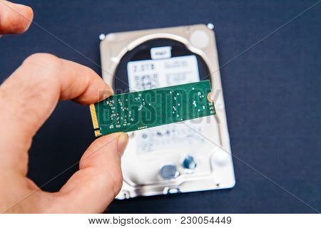 Man holding fast ssd flash memory disk drive with old HDD platter hard disk drive in the background - computer upgrade poster