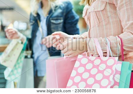 Women with shopping bags shopping at retail mall