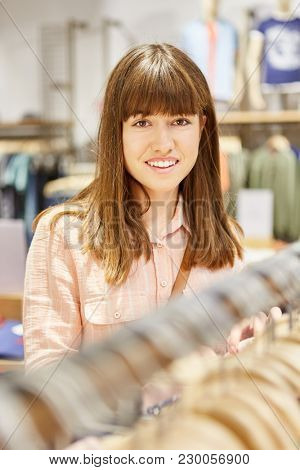 Brunette teenager as a customer in a boutique shopping for clothes