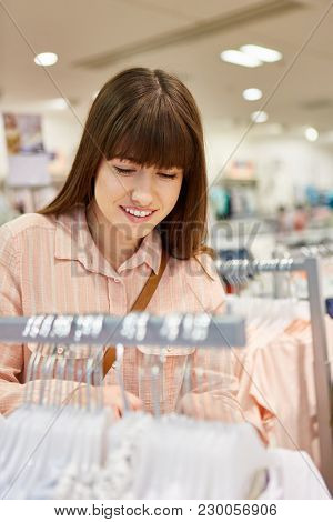 Smiling young woman shopping for clothes in a fashion store while shopping