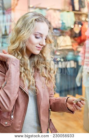 Young blonde woman shopping with a loyalty card in front of a boutique