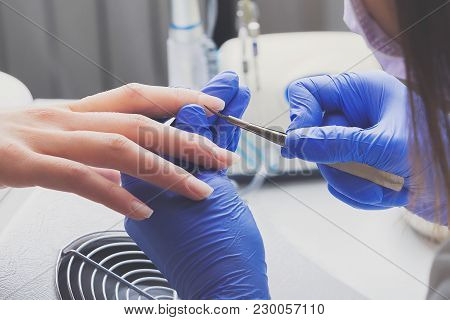 Closeup Shot Of Manicurist In Blue Rubber Gloves And Medical Mask Removes Cuticle On Female Nails Us