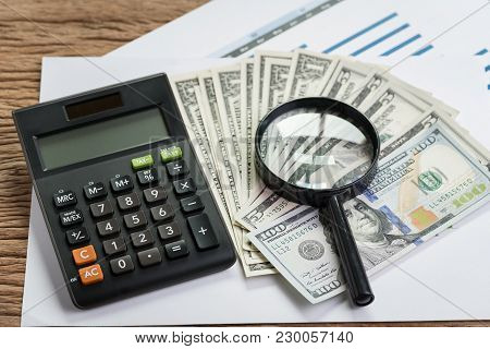Tax, Searching For Yield Or Financial Report Review Concept, Magnifier Glass On Pile Of Us Dollar Ba