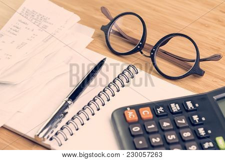 Cost And Expense Calculation Concept, Eyeglasses On Th Table With Black Pen On Paper Notepad With Pi