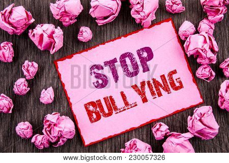 Handwriting text showing Stop Bullying. Business photo showcasing Awareness Problem About Violence Abuse Bully Problem written Pink Sticky Note Paper Folded Paper wooden background poster