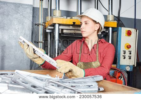 Young woman in metallurgy workshop as blue collar worker