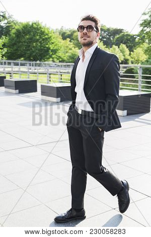 Male Businessman Or Worker In Black Suit, Shirt And Sunglasses With Hands In Pockets Look Up And Wal