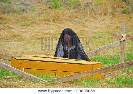 Mourning Widow next to coffin