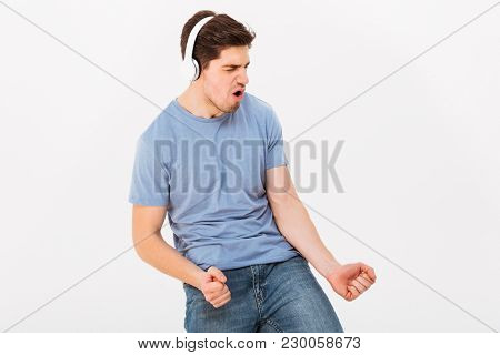 Photo of adult smiling guy with short dark hair listening to music via headphones and expressing pleasure on face isolated over white background