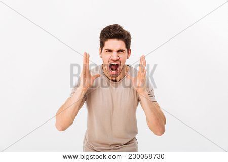 Photo of aggressive or irritated man screaming on camera while lifting hands to face isolated over white background