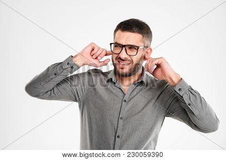 Picture of displeased businessman standing isolated over white background covering ears.