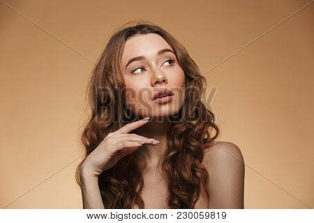 Beauty portrait of half naked thoughtful woman 20s with auburn hair looking aside with interest isolated over beige background