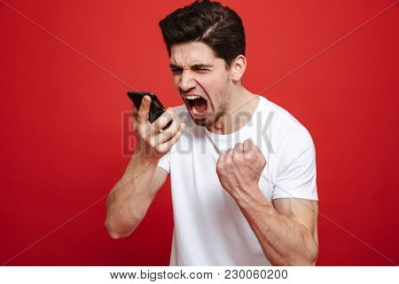 Portrait of a furious young man in white t-shirt yelling at mobile phone isolated over red background