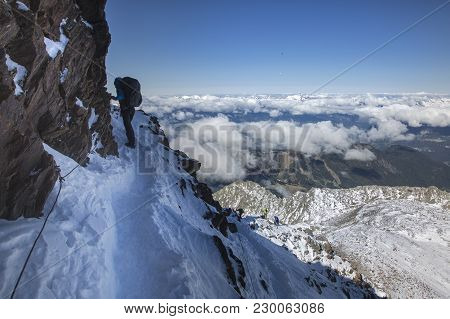 Mountaineering Ascending To The Top Above The Clouds In French Alps