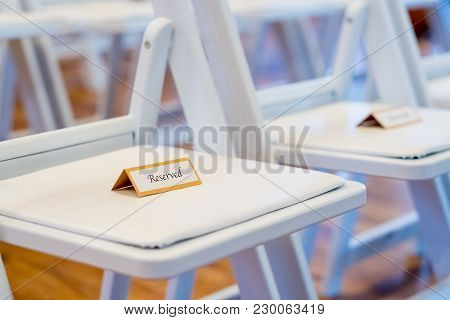 Reserved Sign On Chairs At A Wedding Ceremony Reserving Spots For The Family To Sit.