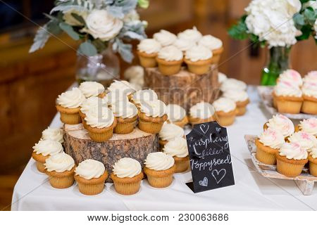 Wedding Dessert Table Full Of Cupcakes Of Various Flavors With Chalkboard Signs To Show What Options