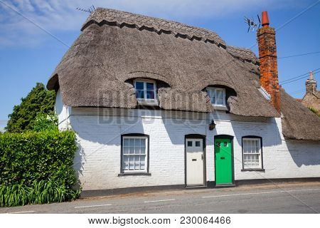 A typical traditional English country thatched house or cottage with white walls in rural Southern England UK