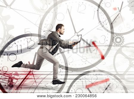 Business Man Runs Fast With A Laptop On A Background Of Clocks