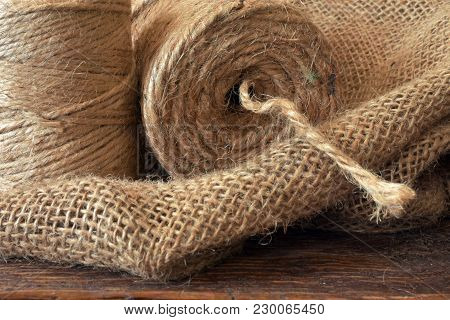 A Close Up Image Of Two Spools Of Craft Cord On A Burlap Sack.