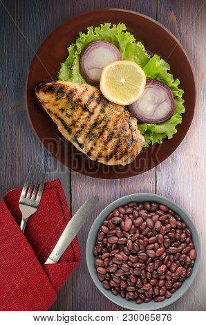 Grilled Chicken Fillet With Vegetables (lemon, Salad, Onion) On A Wooden Background. Chicken Fillet