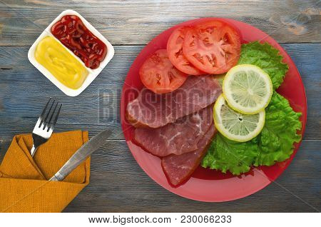 Ham With Salad, Tomato And Lemon On A Plate. Ham On A Wooden Background .ham Top View