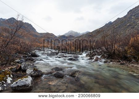 A Quickly Moving Stream Running Through A Archangel Valley In The Alaskan Mountains Near Hatcher Pas