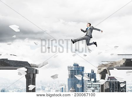 Businessman Jumping Over Gap With Flying Paper Planes In Concrete Bridge As Symbol Of Overcoming Cha