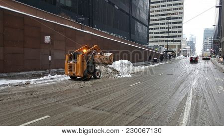Snow Being Dumped Into A Snow Pile With A Case 40xt Skid Steer Loader After A Winter Snowstorm, Chic