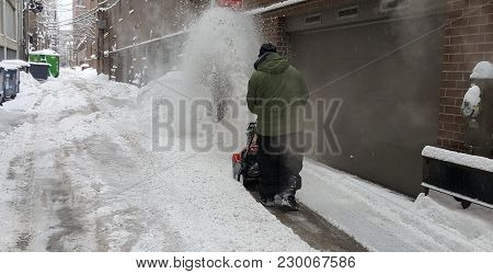 Man Pushing Snowplow In A Back Alley After A Winter Snowstorm In Chicago