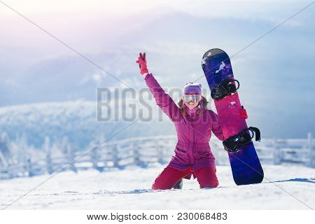Snowboarding. Young Woman Sits On Snow And Holds Snowboard, Raises Her Hand Upwards And Smiles.