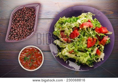 Vegetarian Food . Salad Of Cabbage Tomato On A Plate On A Wooden Background. Healthy Food