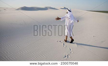Cheerful Muslim Guy Arabian Uae Sheikh Walks Along White Sand Of Wide Desert On Warm Summer Evening.