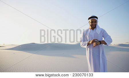 Handsome Male Muslim Sends Message To Friend Using Modern Smart Watch Device, Which Worn On Hand And