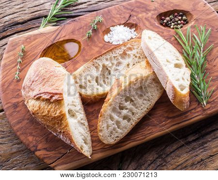 Slices of ciabatta with rosemary herb on the serving wooden tray. Top view.