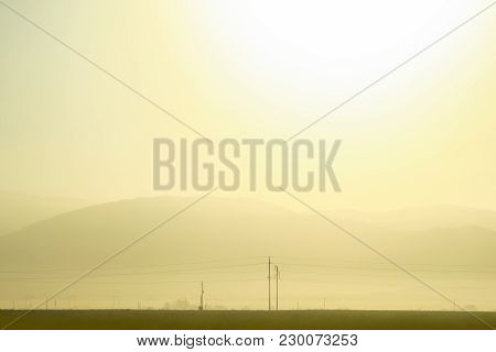 Panoramic View Of A Beautiful Sunrise In Golden Tones With Mountains In The Background And Some Pole