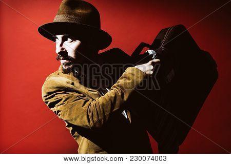Man Posing In Studio With Suitcase In Hands